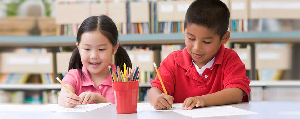 A young girl in a pink shirt and a boy in a red shirt sit at a table in a library and complete worksheets while smiling.