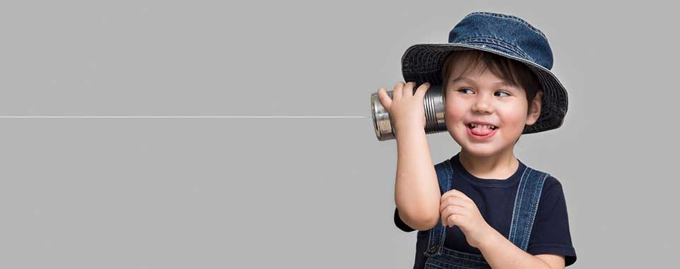 Smiling little boy in a bucket hat and overalls holding a can with a string attached to his ear.